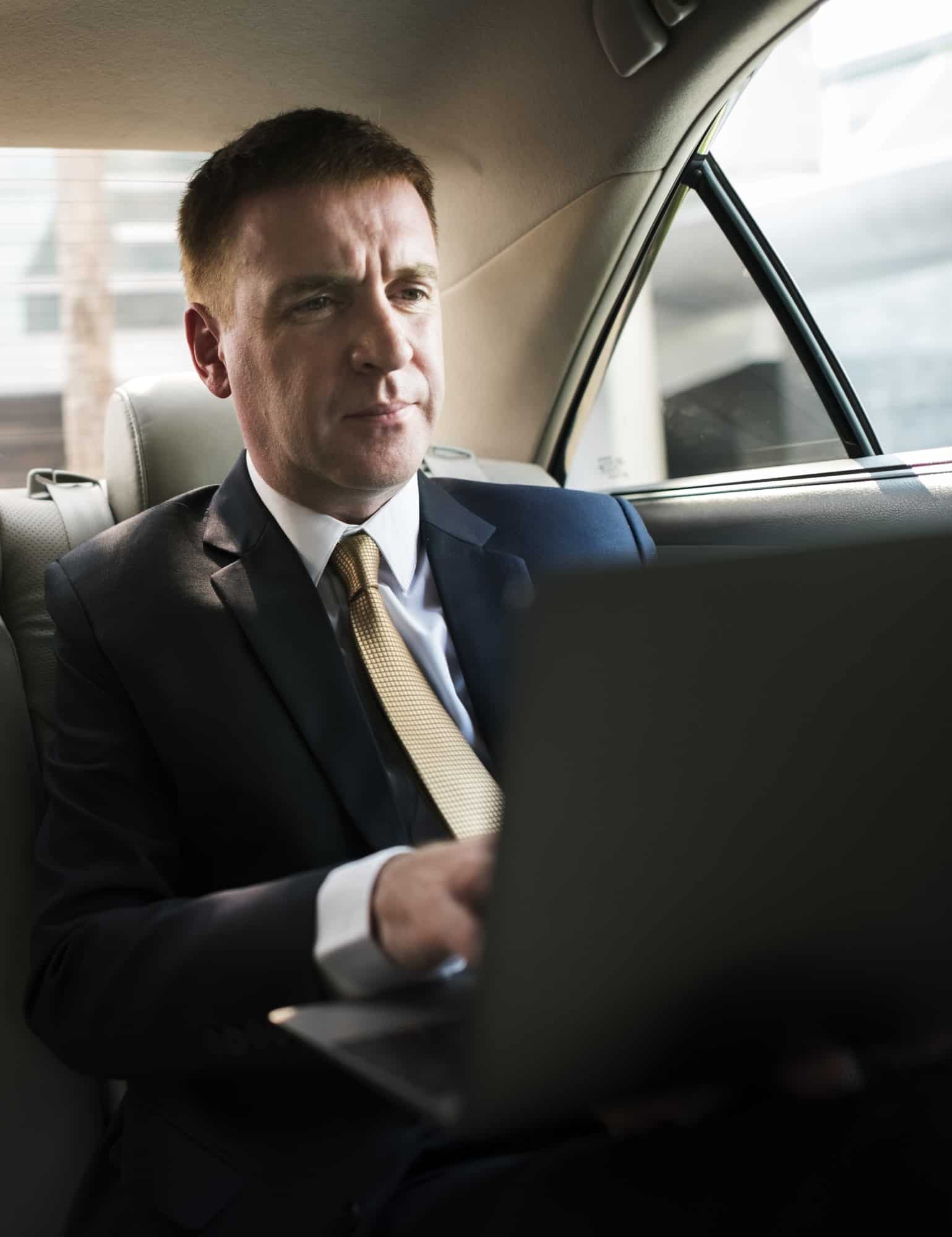 Businessman inside a car working on his laptop